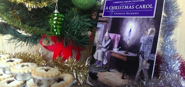 A Christmas Carol by Charles Dickens, alongside a christmas tree, tinsel and mince pies