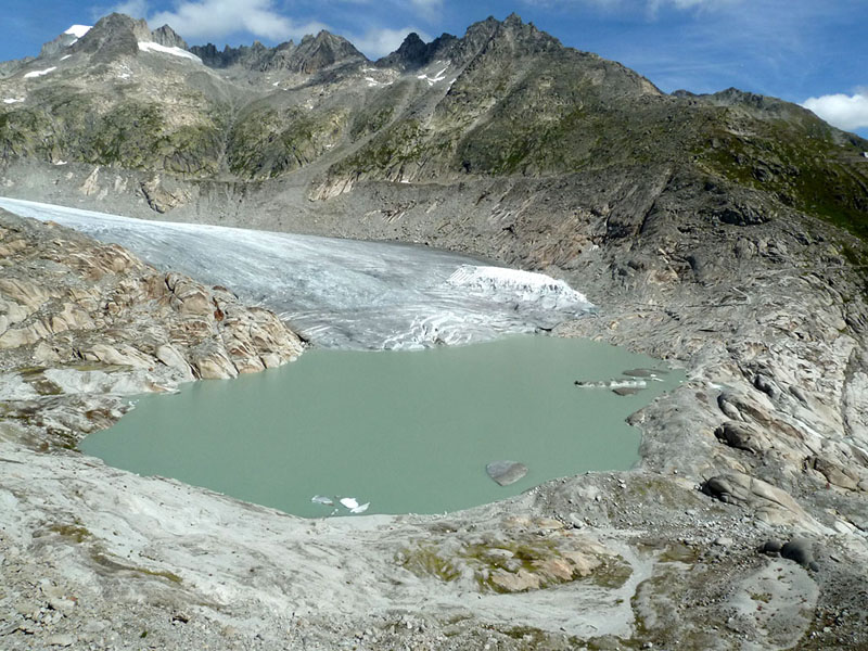 As glaciers recede, many lakes have formed in the high mountains of the world such as at Rhone glacier, Swiss Alps (note at the right margin of the glacier extensive coverage of glacier by geotextiles to 'save' the local ice cave for tourists)