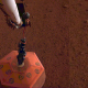 The robotic arm on NASA's InSight lander places a seismometer onto the surface of Mars.(credit: NASA/JPL-Caltech).