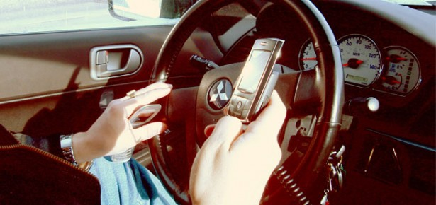 Woman using 2 cellphones whilst driving a car.